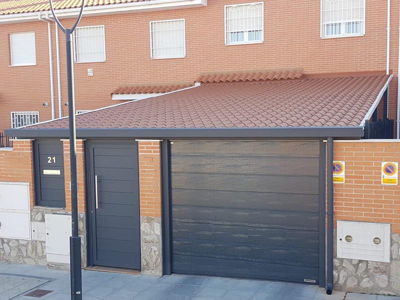Puerta seccional hormann, puerta y valla de aluminio soldado, porche de imitación teja.